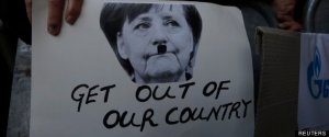 Protesters hold a photograph of German Chancellor Merkel painted to make her look like Adolf Hitler during an anti-bailout rally outside the parliament in Nicosia