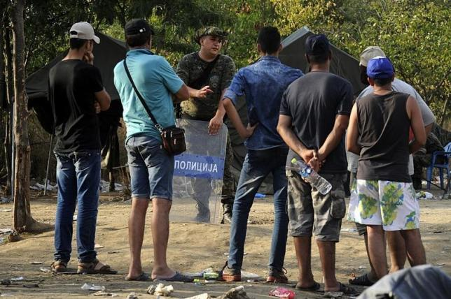 A Macedonian police officer talks with migrants standing on the Greek side at the Greek-Macedonian border, August 20, 2015. REUTERS/Alexandros Avramidis